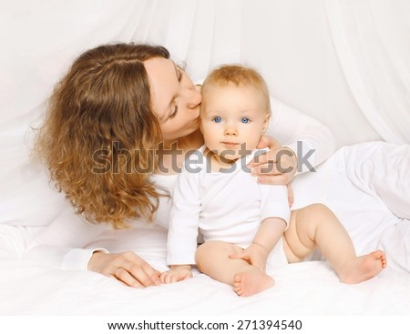 Happy mother kissing baby at home lying on the bed - stock photo