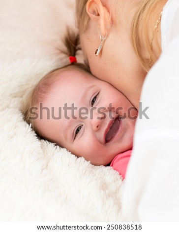 Happy mother kissing baby daughter lying on bed - stock photo