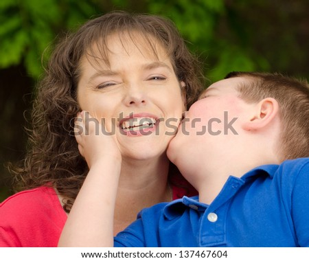 Happy mother laughing at sloppy kiss from son - stock photo