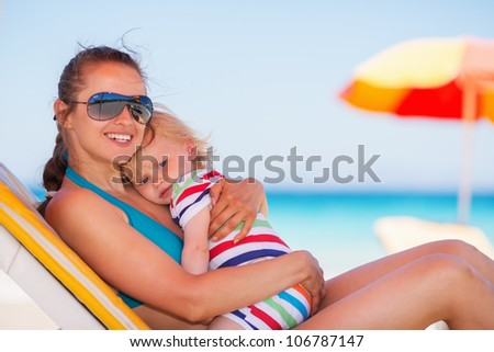 Happy mother laying on sun bed and hugging baby