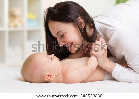 Happy mother looking at baby son in bedroom