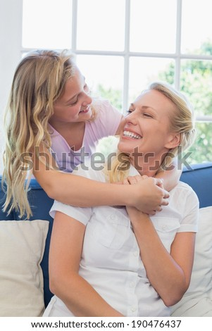 Happy mother looking at daughter embracing her from behind in living room