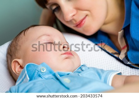 happy mother looking on sleeping baby - stock photo