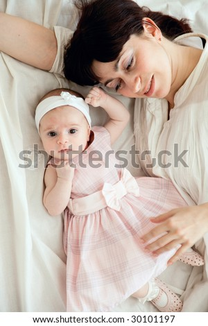 happy mother lying with her newborn daughter