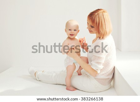 Happy mother playing with baby home in white room  - stock photo