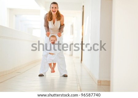 Happy mother playing with baby outdoor - stock photo