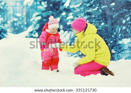 Happy mother playing with child in snowy winter day - stock photo