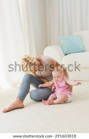 Happy mother playing with her baby girl at home in the living room