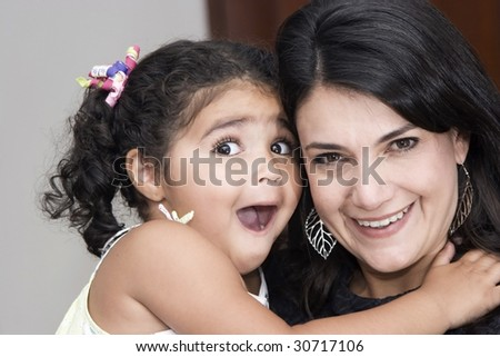 Happy mother playing with her daughter at home