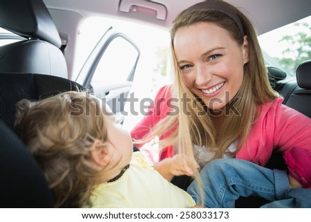 Happy mother playing with her daughter in their car
