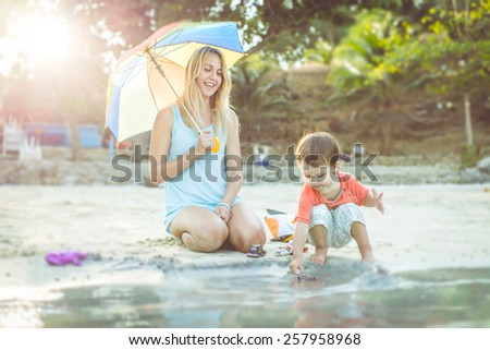 happy mother playing with her kid on the beach. concept about family - stock photo