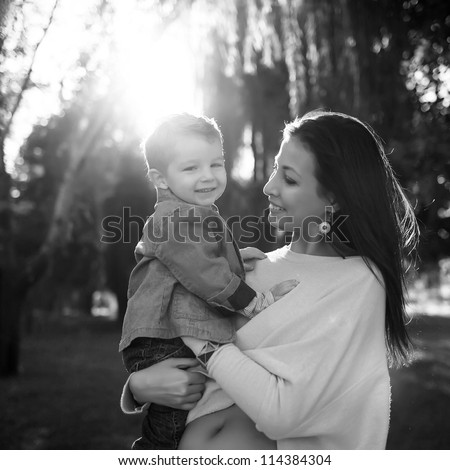 happy mother playing with her son in the park,black and white - stock photo