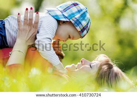Happy mother playing with her toddler during spring day at the park - stock photo