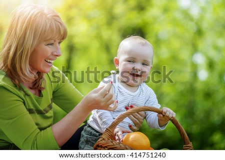 Happy mother playing with her toddler during spring day at the park. - stock photo