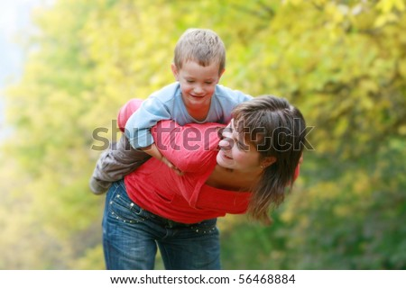 happy mother playing with son outdoors