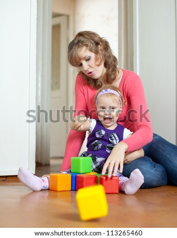 Happy mother plays with baby  in home interior - stock photo