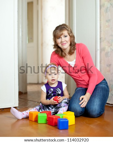Happy mother plays with baby  in home interior