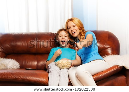 Happy mother pointing at TV and son laughing - stock photo
