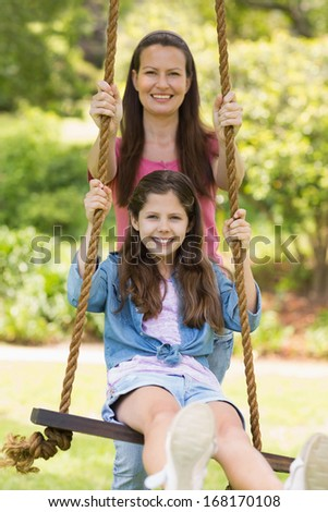 Happy mother pushing daughter on swing in playground - stock photo