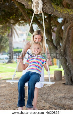 Happy mother pushing her daughter on a swing in a park - stock photo