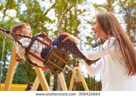 happy mother pushing laughing son on swing in a park - stock photo