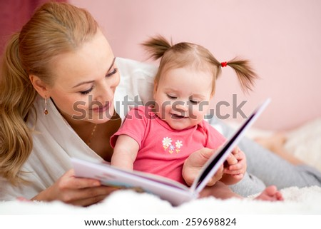happy mother read a book to baby girl at home - stock photo