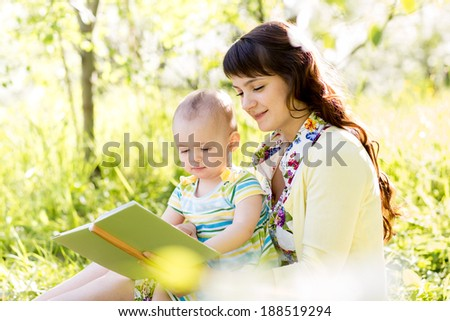 happy mother reading a book to child outdoors - stock photo