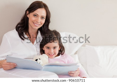 Happy mother reading a story to her daughter in a bedroom - stock photo
