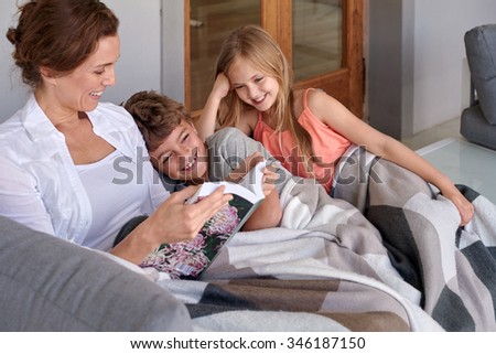Happy mother reading her novel cuddled on couch with cheerful happy smiling son and daughter children
