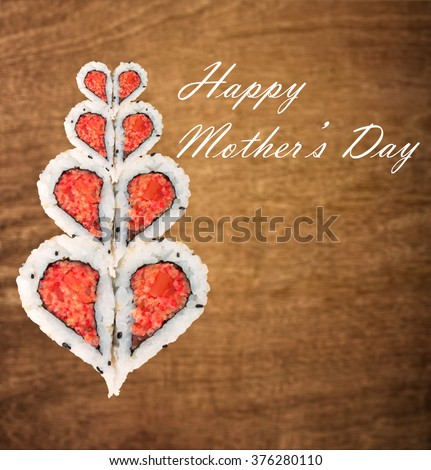 Happy Mother's day concept with sushi forming heart shapes against wooden background - stock photo