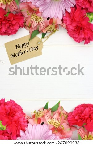 Happy Mother's Day gift tag with double border of pink flowers against a white wood background       - stock photo