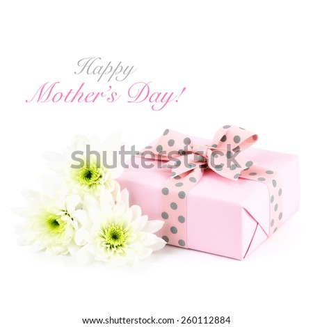 Happy Mother's day greeting card with a wrapped pastel pink gift and chrysanthemum flowers on white background with copy space for your text - stock photo