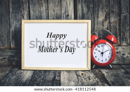 Happy mother's day message on white board and red retro clock  by wooden background. - stock photo
