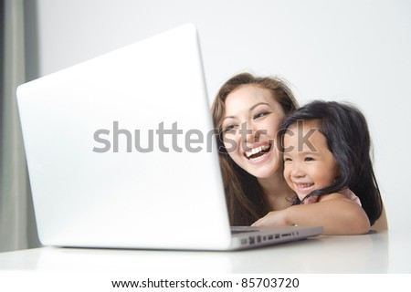 Happy Mother showing daughter how to use a computer - stock photo