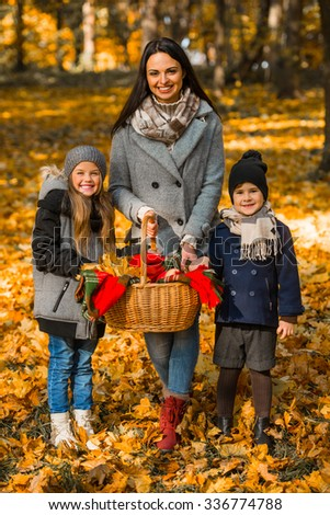 Happy mother, son and daughter during a walk in the autumn park - stock photo