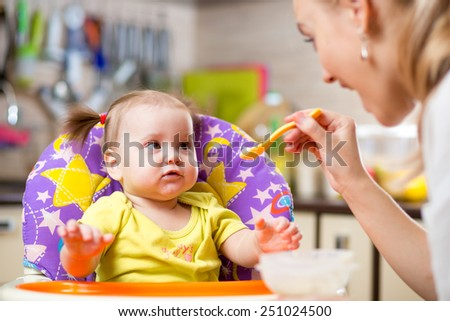 Happy mother spoon feeding child toddler indoors - stock photo