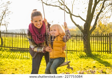 Happy mother swinging child outdoors - stock photo
