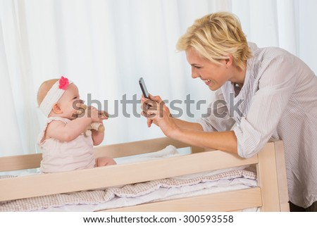 Happy mother taking a picture of her baby girl at home in bedroom - stock photo