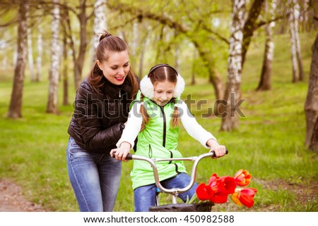 happy mother teaches his daughter to ride a bike. Mother holds daughter from falling