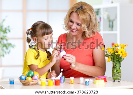 happy mother teaches kid daughter to paint easter eggs - stock photo