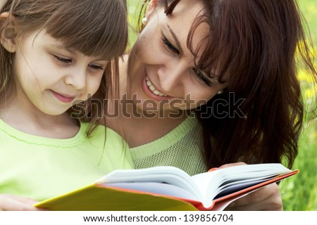 Happy mother teaching to read her small girl�¢?? education time - stock photo
