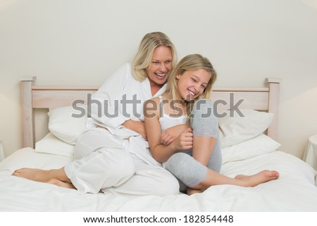 Happy mother tickling daughter in bed at home