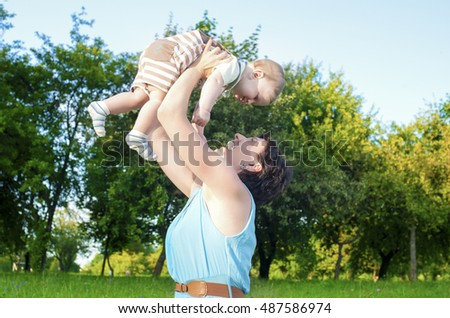 Happy Mother Tossing Up Her Kid While Playing with Him in Park Outdoors. Horizontal Image