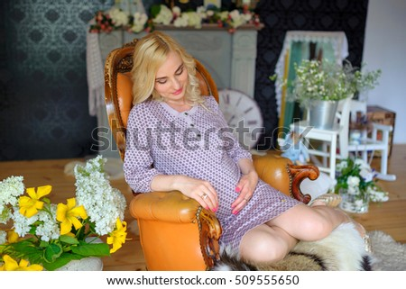 happy mother waiting for the child's birth, sits on a suitcase and pensively holds flowers in hand, happy pregnancy, motherhood