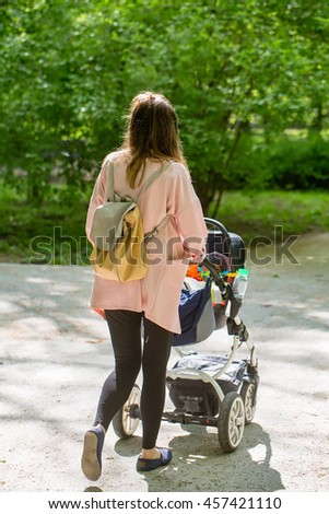 Happy mother walking with baby stroller in park - stock photo