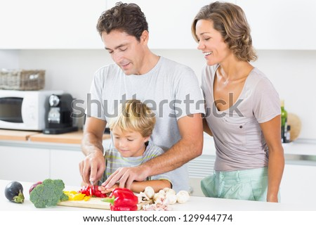 Happy mother watching father teaching son to chop vegetables in kitchen - stock photo