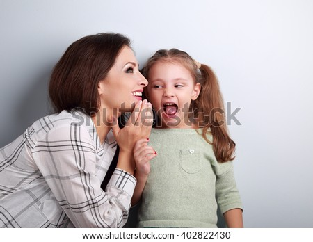 Happy mother whispering the secret to her surprising cute girl in ear on blue background - stock photo