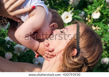 Happy mother with a baby in nature - stock photo