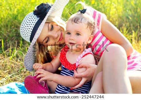Happy mother with a baby in nature are resting - stock photo