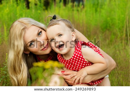 Happy mother with a baby on nature background